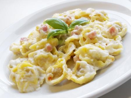 tortellini: Italian cuisine background  Close-up of delicious stuffed pasta tortellini with cream, ham and basil on white dish