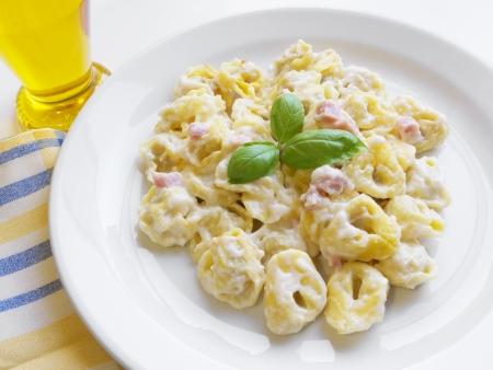 tortellini: Italian cuisine background  Delicious stuffed pasta tortellini with cream, ham and basil on white dish  Stock Photo