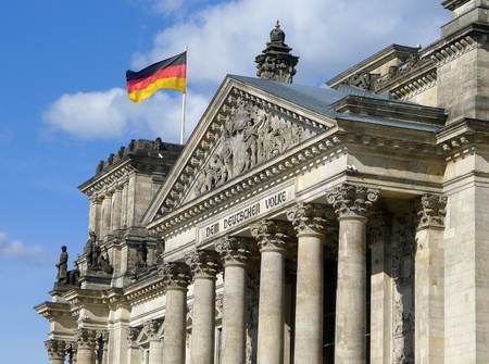 Lateral view of Reichstag Building with waving German flag in a beautiful summer day with blue sky, Berlin, Germany, Europe
