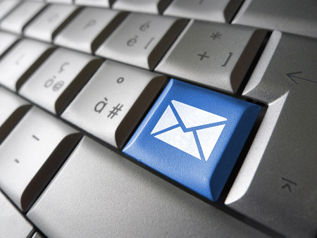 Contact us Internet concept with e-mail icon and symbol on a blue laptop computer key for website, blog and on line business  photo