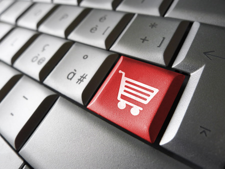 Web and Internet on line shopping concept with basket icon and symbol on a red laptop computer key for website and online business. photo