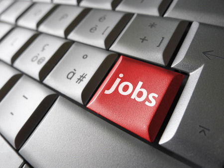 Online job search concept with jobs sign and symbol on a red laptop computer key for website and online business. photo