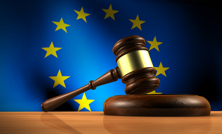 European Union law, legislation and parliament concept with a 3d rendering of a gavel on a wooden desktop and the EU flag on background.