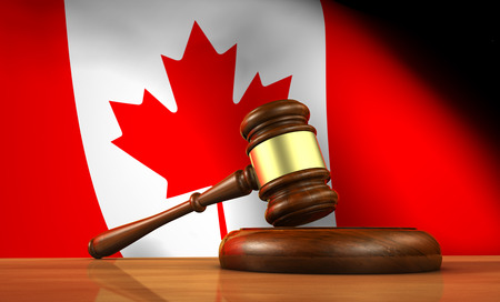 computer law: Law and justice of Canada concept with a 3d rendering of a gavel on a wooden desktop and the Canadian flag on background.