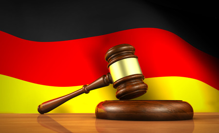 computer law: Law and justice of Germany concept with a 3d rendering of a gavel on a wooden desktop and the German flag on background.