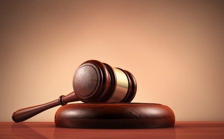 Judge, law, lawyer and Justice concept with a close-up 3d rendering of a gavel on a wooden desktop with dark red-brown background. Stock Photo