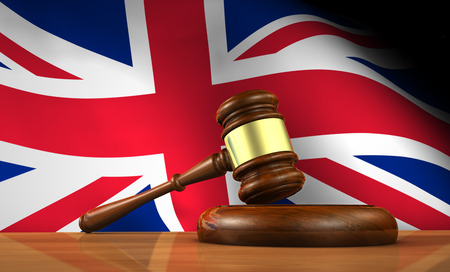 constitutional law: Law and justice of United Kingdom concept with a 3d rendering of a gavel on a wooden desktop and the Union Jack Uk flag on background.