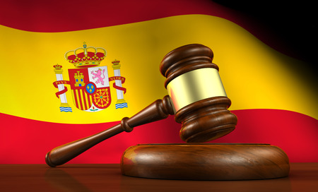 constitutional: Law and justice of Spain concept with a 3d rendering of a gavel on a wooden desktop and the Spanish flag on background. Stock Photo