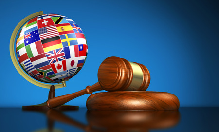 International law systems, justice, human rights and global business education concept with world flags on a school globe and a gavel on a desk on blue background.
