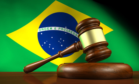 constitutional law: Law and justice of Brazil concept with a 3d rendering of a gavel on a wooden desktop and the Brazilian flag on background.