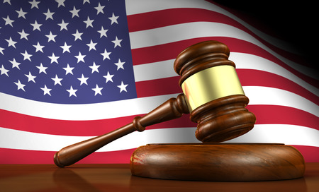 us government: USA law and justice of The United States of America concept with a 3d render of a gavel on a wooden desktop and the flag of US on background.
