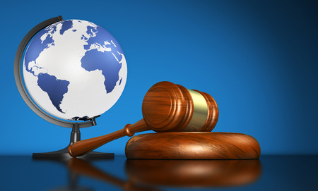 universal: International law systems, justice, human rights and global business education concept with world map on a school globe and a gavel on a desk on blue background.