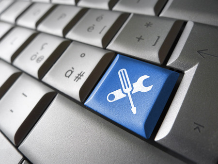 Assistance and computer service concept with toolkit icons and symbol on a blue laptop computer key for website and online business. Stock Photo