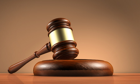Judge, law, lawyer and legality concept with a close-up 3d render of a gavel on a wooden desktop with dark red-brown background.
