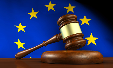 justice: European Union law, legislation and parliament concept with a 3d render of a gavel on a wooden desktop and the EU flag on background.