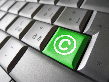 copyright symbol: Digital copyright web content and Internet concept with copyright symbol and icon on a green laptop computer key for blog, website and online business.
