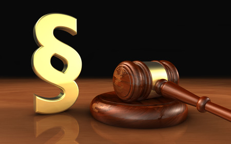 Law, legality and legal system concept with a golden paragraph symbol and a wooden gavel on a desktop with black background. Archivio Fotografico