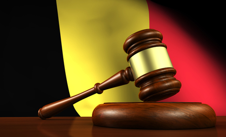 government regulations: Belgium law, legal system and justice concept with a 3d Rendering of a gavel on a wooden desktop and the Belgian flag on background. Stock Photo