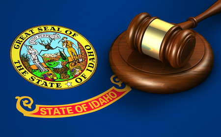 legality: Idaho US state law, legal system and justice concept with a 3D rendering of a gavel on the Idahoan flag on background. Stock Photo