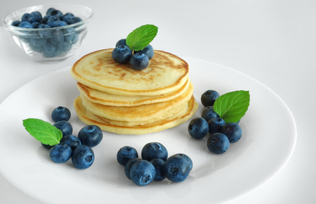Blueberry pancakes gourmet breakfast background with mint leaves and maple syrup. Stok Fotoğraf