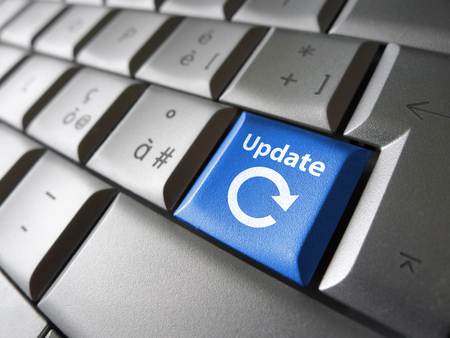 updating: Website and Internet update concept with icon and sign on a laptop computer key. Stock Photo