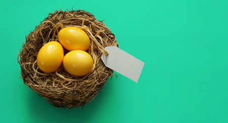 Easter banner background with three yellow Easter eggs in a wooden nest with copy space and a blank white paper price tag for greeting message.