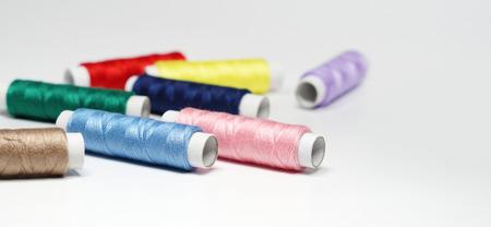 Nähfäden in verschiedenen Farben hautnah auf weißem Hintergrund mit Kopierraum.