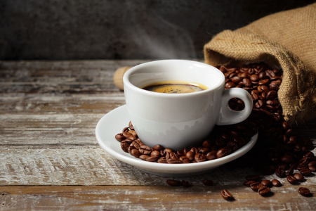 Coffee cup and roasted coffee beans in a burlap sack on a rustic wooden table on rusty vintage background. Stok Fotoğraf