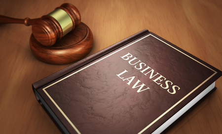Business law and commercial law concept with sign printed on a book and a judge gavel on a wooden desk 3D illustration.