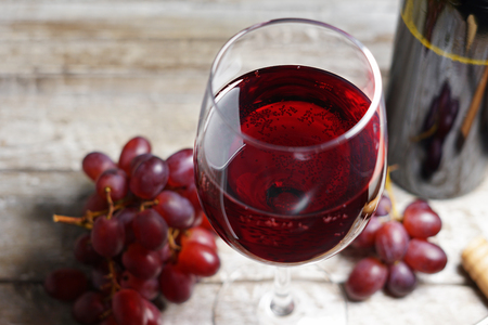 Glass of red wine on a wooden table in a rustic and vintage wine bar with grapes fruit and a bottle of wine on background close up view.