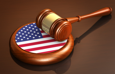 American law and justice of The United States of America concept with a 3d rendering of a judge gavel and the flag of USA on a wooden desk.