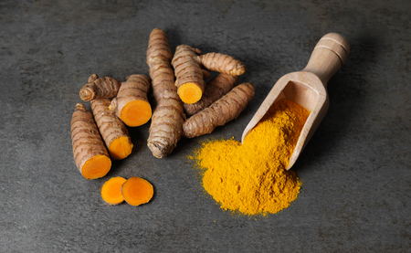 Turmeric powder healthy spice Asian food close up top view of turmeric root sliced and a wooden bailer on a rustic dark grey kitchen board.