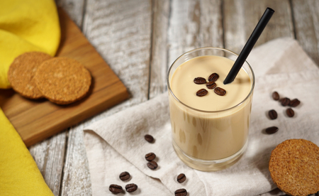Cold coffee yogurt milkshake smoothie drink in a glass topped with coffee beans and whole grain biscuits on a wooden rustic table with copy space. Stok Fotoğraf