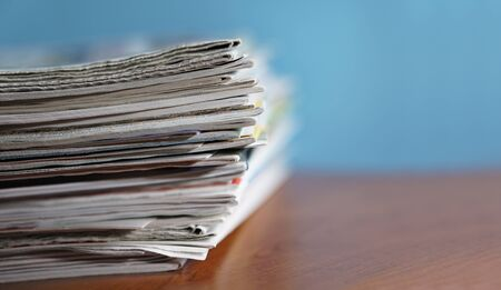 Stack of newspapers and magazines on a wooden desk and blue background selective focus close-up view with copyspace.