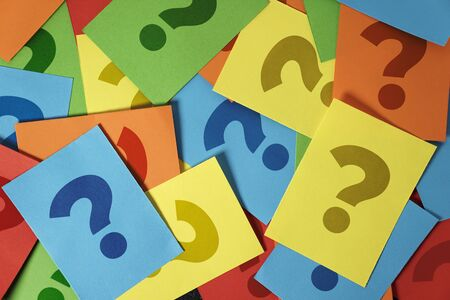 Question mark symbol and sign on many colorful note papers, customer questions and business assistance concept top view background.