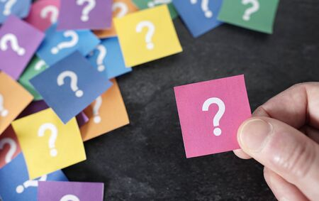 Customer business questions concept with a close up view of a male hand holding a pink paper with question mark symbol and many others colorful papers on background.