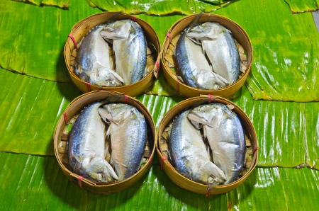 steamed fish Thai style,Steamed fish in a wicker basket placed on a banana leaf  photo