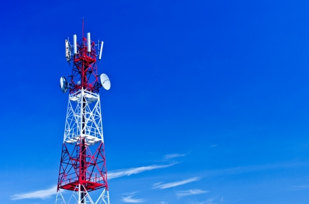Telecommunications tower, painted white and red in a day of clear blue sky  photo