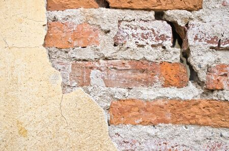 old brick wall with cracked stucco layer background Stock Photo