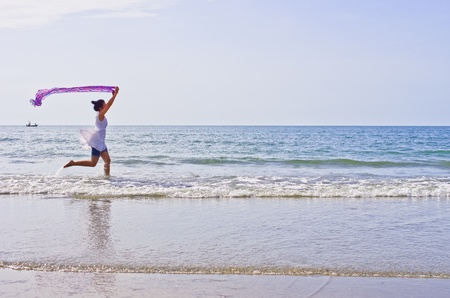 Woman ran a cloth held outdoors on the beach.