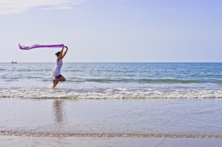 Woman ran a cloth held outdoors on the beach. photo