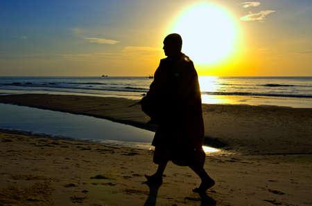 Monk on Hua Hin beach with silhouette photo