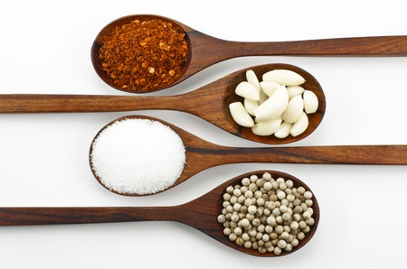 Cayenne pepper, sugar, garlic and pepper,Arranged in a wooden spoon. photo