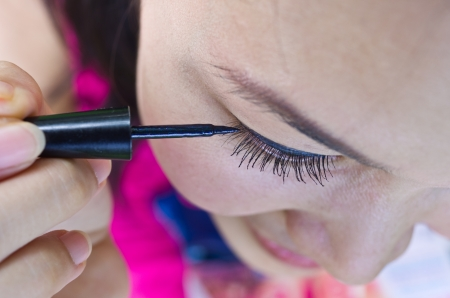 Closeup of Asian Woman Putting Mascara Makeup Eyes