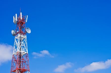 Telecommunications tower, painted white and red in a day of clear blue sky. 版權商用圖片
