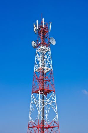 Telecommunications tower, painted white and red in a day of clear blue sky. photo