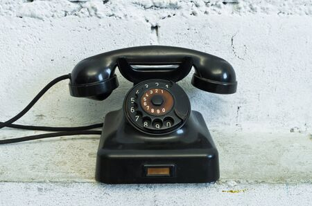dial plate: Old black telephone with rotary dial in white room Stock Photo