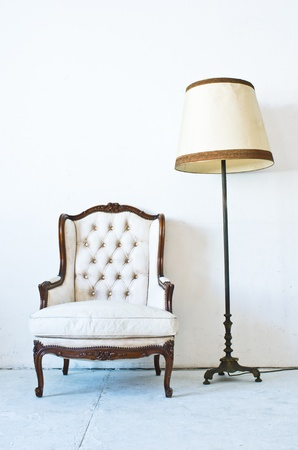 Vintage luxury White sofa Armchair with lamp stand in white room. photo