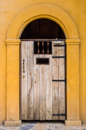 Antique wooden arched entrance. With yellow walls. Stock Photo - 16858742