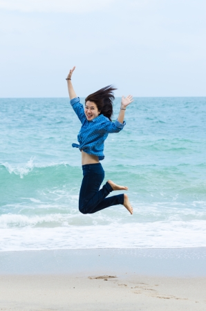 Portrait of happy young woman jumping while enjoying on beach photo